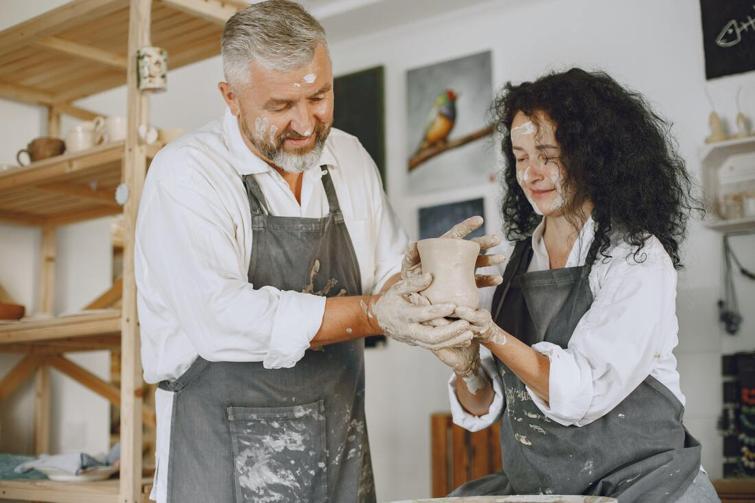 Old man with young woman molding a clay pot